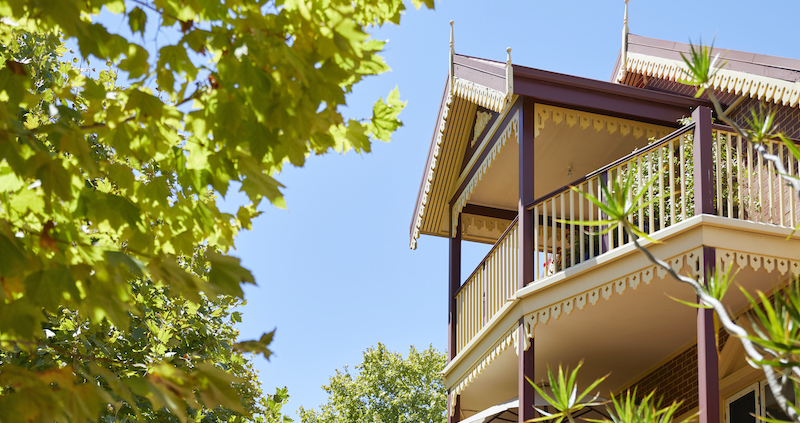 A heritage house with plane trees in the foreground