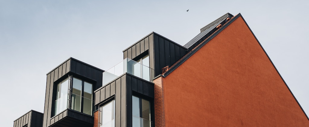 A medium density house with a red wall and black rooms coming out in blocks on the outside
