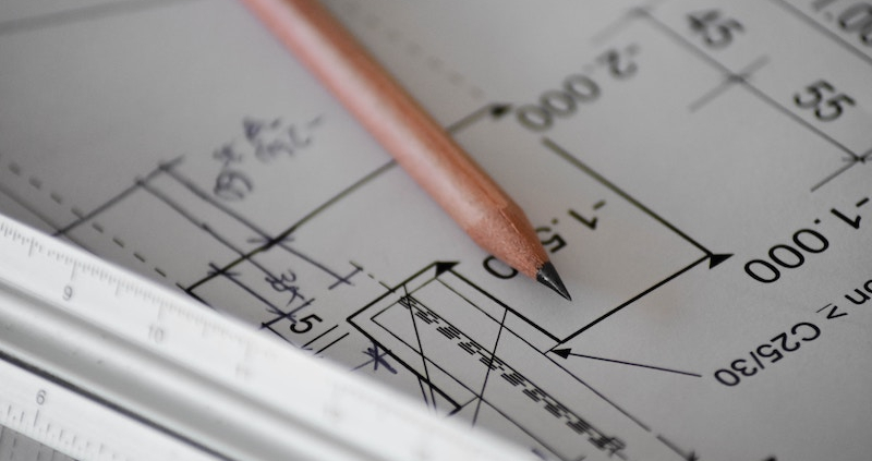 Rule and pencil on top of an architectural drawing of a house