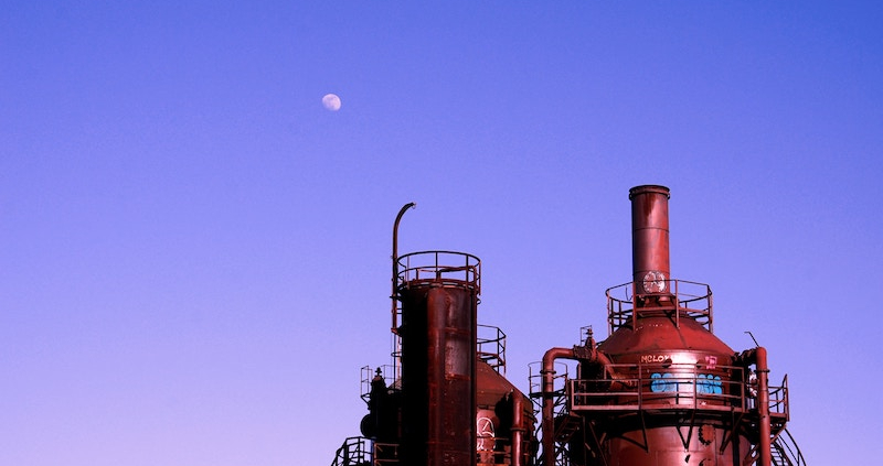 A refinery with a dusky sky in the background