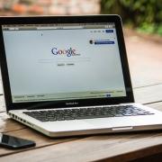 Laptop on desk showing google