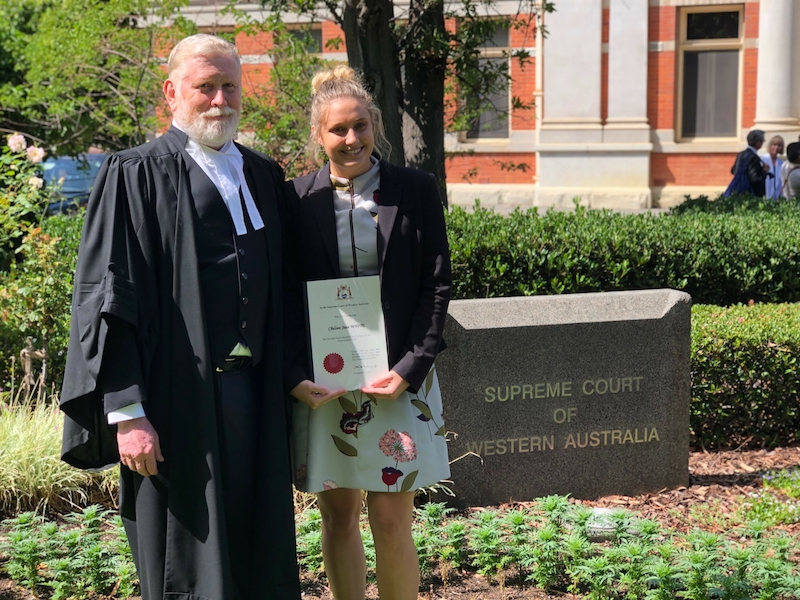 Glen McLeod in court robes on the left standing with Chelsea White, holding her admission certificate. Both are smiling because it is a great day!