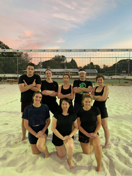 The team Justice Served wearing an all black uniform on the beach volleyball court with a beautiful dusky sky behind.