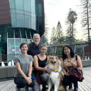 Team Glen McLeod Legal, left to right: Lea Hiltenkamp, Glen McLeod, Chelsea White, Gary the therapy dog and Emiko Watanabe in front of the bell tower at the Law Access Walk for Justice
