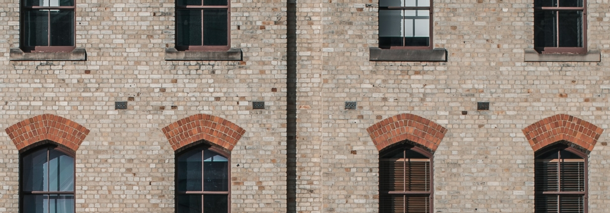 A photo of a building facade with light brown bricks and windows. The windows have red bricks at the top as a design feature.
