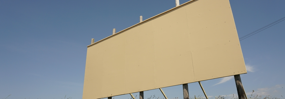 An empty billboard in a field